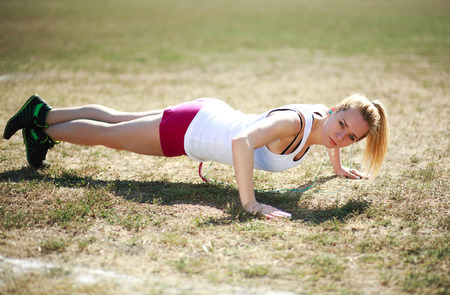 Young woman doing push ups exercise, workout on grass field photo