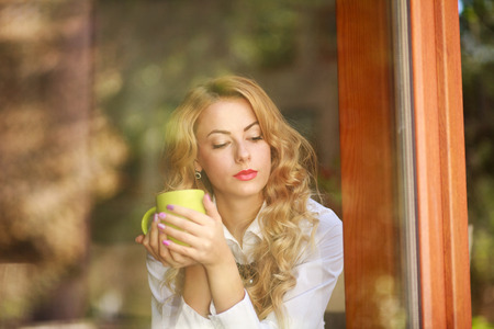 Pensive woman drinking coffee at home, looking out the window, view from outside Stok Fotoğraf