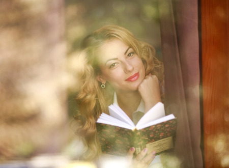 Smiling woman with book at home, view through window glass with reflections and flares photo