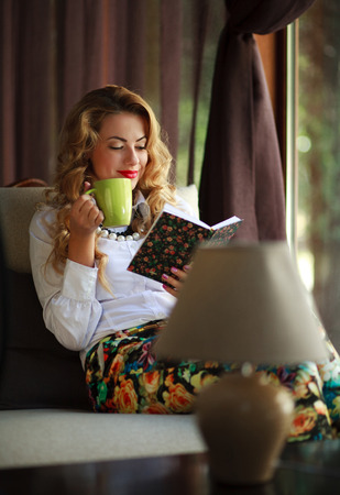 Happy young woman drinking coffee and reading book on couch near the window at home photo