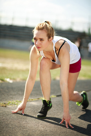 Young woman on a treadmill is ready to start, exercising outdoors photo