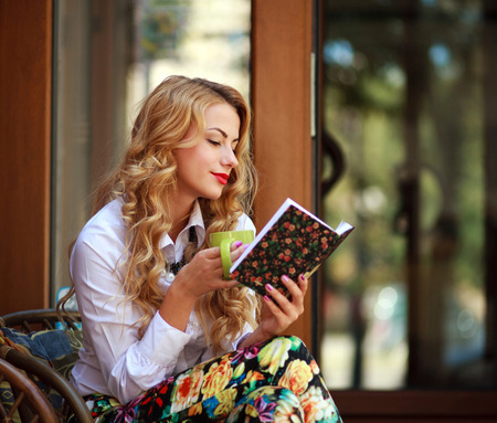Attractive young woman reading book while drinking coffee at sunny day sitting in a chair outdoors Stok Fotoğraf