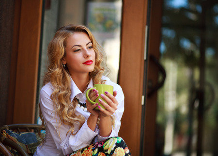 green house: Pensive woman sitting with coffee cup and has a rest in spring cafe outdoors and dreaming looking far away Stock Photo
