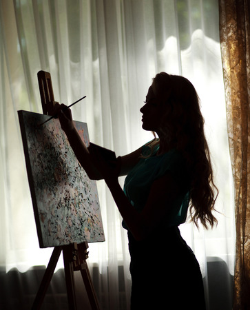 Silhouette woman artist draws paint picture on easel, backlight portrait indoor Stok Fotoğraf