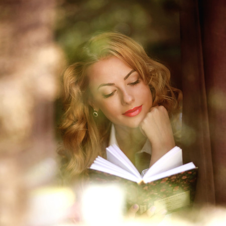 view through: Beautiful girl reading a book indoors, the view through window with reflections Stock Photo