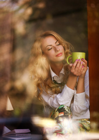 Dreamy woman with a cup of coffee in cafe, enjoying the aroma of beverage, view through the window Stock Photo