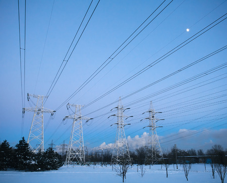 power tower: Electricity pylons and power high voltage power tower in winter evening Stock Photo