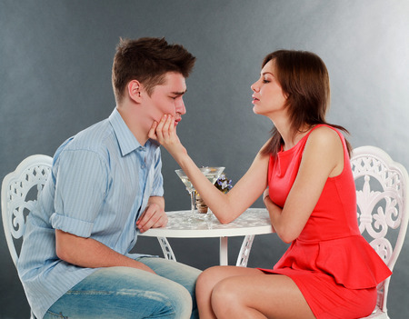lazybones: Girl with her drunk and sad boyfriend at table, in studio isolated on gray Stock Photo
