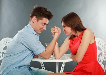 wrestle: Young happy couple challenge fighting in arm-wrestling at table, in studio isolated on gray Stock Photo