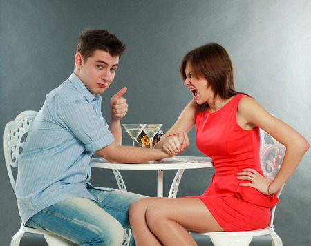 Young aggressive woman winning fighting in arm-wrestling at table, in studio isolated on gray