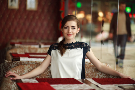 Beautiful young woman alone waiting at a table in a restaurant photo