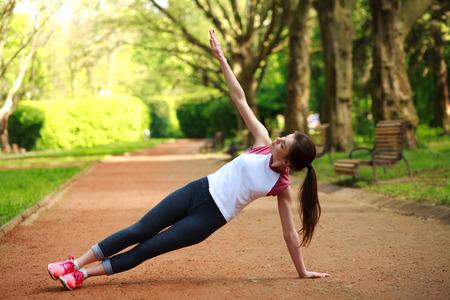 Muchacha juguetona ejercicio al aire libre en el parque de verano, entrenamiento físico al aire libre