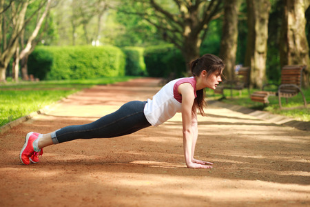 girl working out: Sportive girl working out doing push ups press exercise in summer park