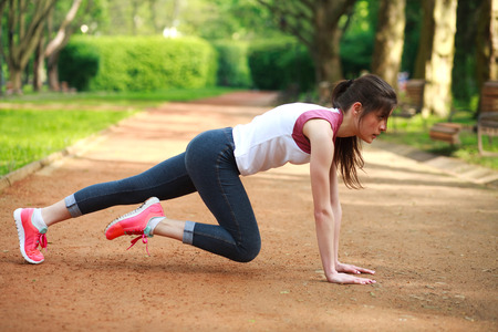 push: Sportive girl working out doing push ups press exercise in summer park