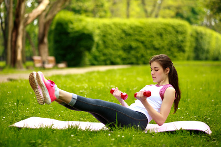abdominal fitness: Mujer joven juguetona que estira con pesas, haciendo ejercicios de fitness en el parque verde