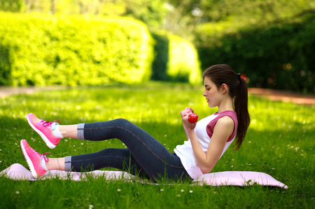 Sportive young woman stretching with dumbbells, doing fitness exercises in green park Stok Fotoğraf