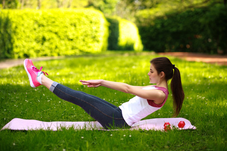 Sportive young woman stretching, doing fitness exercises in green park, workout outdoors