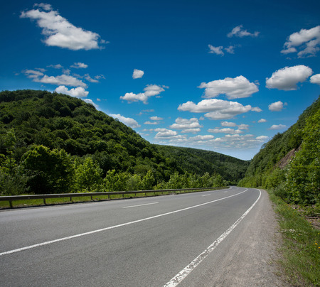 highway: Empty asphalt road highway in the forested mountains, on the background a cloudy sky