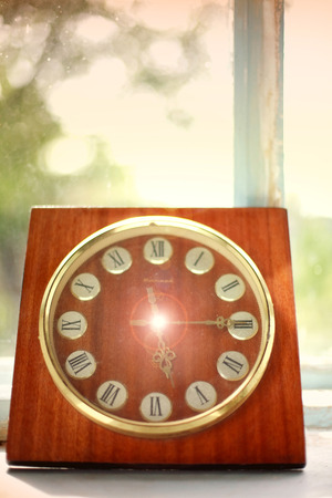 wooden clock: Vintage wooden clock at the old rural window, concept past time
