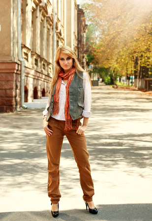 clothing model: Fashion woman in retro style on a city street in autumn under the warm rays of sun