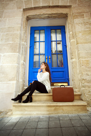 behold: Woman traveler with a suitcase sitting dreamy at the threshold of his house