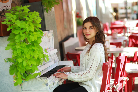 old piano: Romantic girl playing on an old piano in street cafe Stock Photo