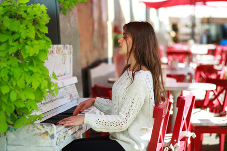 old piano: Girl playing on an old piano in street cafe