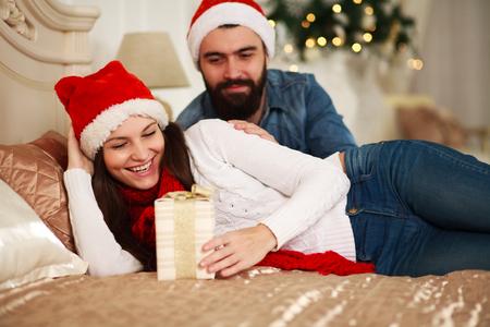 marido y mujer: El hombre presenta regalo de la muchacha de A�o Nuevo, Navidad pareja en la cama