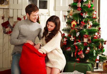 uomo rosso: Coppia felice con un sacco di regali sullo sfondo l'albero di Natale a casa