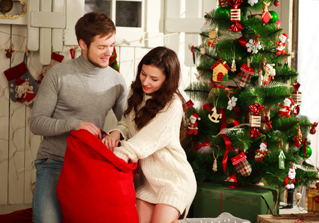 a young man: Happy couple with a bag of gifts on the background of the Christmas tree at home