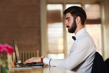 busy beard: Young businessman working at a laptop in the office