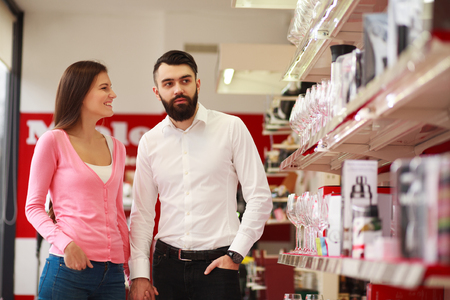 degustating: Young couple in the store on background of shelves with wine glasses Stock Photo