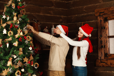 decorates: Cheerful couple decorates a Christmas tree in a country house Stock Photo