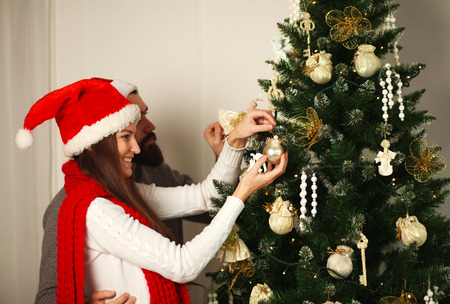 decorates: Joyful couple in red hats decorates Christmas tree