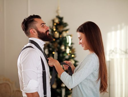 clothe: Girl clothe her boyfriend tie on background Christmas trees