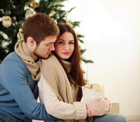 guy portrait: Sad girl with a gift in the embrace of her boyfriend on background Christmas tree Stock Photo