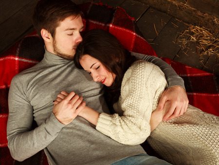 mujer pensativa: Pareja de enamorados que yacen en los brazos del otro en el suelo de una casa de campo