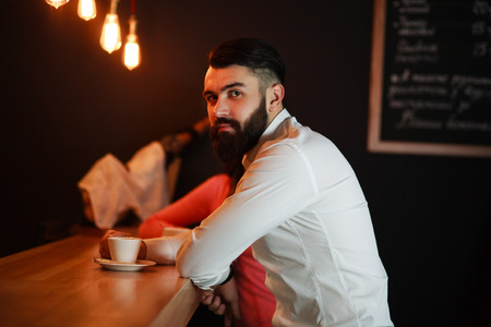 expects: Young business man behind the bar with coffee Stock Photo