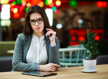 narrator: Young business woman in room with tablet computer at the table Stock Photo