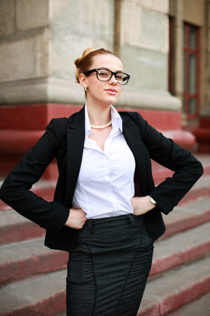exacting: Serious girl student in a business suit in front of a university building Stock Photo