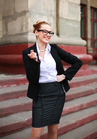 exacting: Cheerful student girl pointing a finger in a business suit on a university background