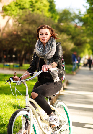 outdoor sport: Pensive young woman riding a bicycle in the green city park Stock Photo