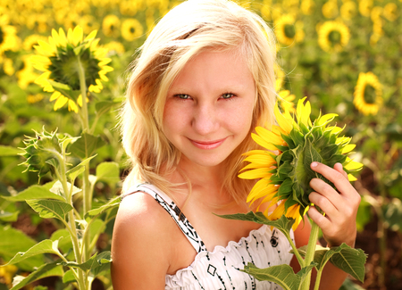 Happy smiling teen girl with sunflowers in summer field