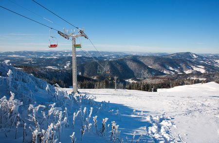 Ski lift in winter snowy mountains on sky background