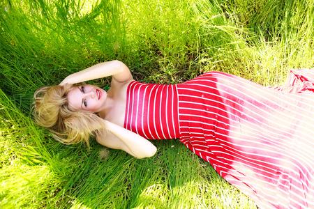 salud sexual: mujer joven de la belleza en un vestido acostado en un prado verde en la hierba