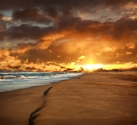 Empty sandy beach and windy sea on the background of dramatic sky cloud Stock Photo