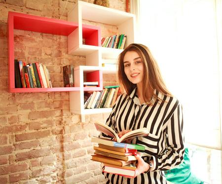 cognicion: Sonriente niña con libros en la biblioteca