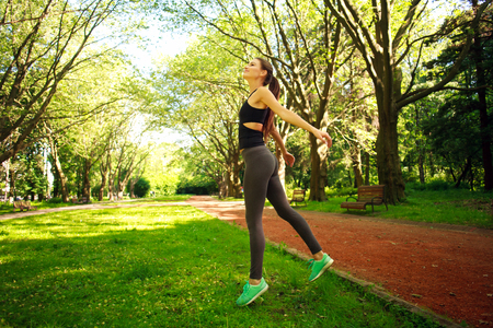 Sportive young fitness woman jumping in summer park, freedom concept