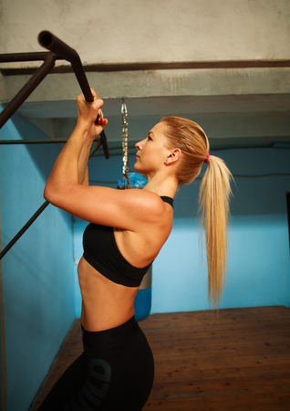 Sporty athlete woman exercising doing pull-ups in the gym from back