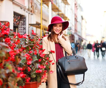 Elegante vrouw in een laag en een purpere hoed op een stad van de straattoerist met bloemen Stockfoto